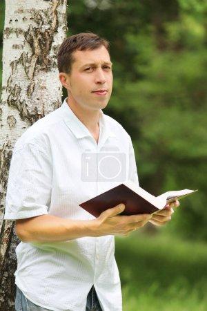 Photo pour Un jeune homme lisant la Bible - image libre de droit