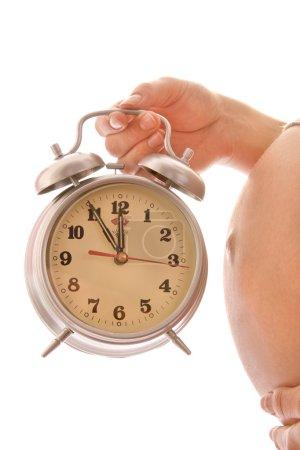 Photo pour La femme enceinte sur fond blanc avec une horloge - image libre de droit