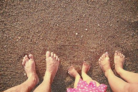 Photo pour Une empreinte de famille dans le sable sur le bord de la mer - image libre de droit