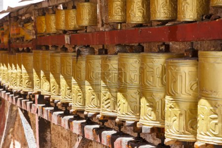 Gold colored Buddhist prayer wheels in Lhasa, Tibet
