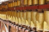 Gold colored Buddhist prayer wheels in Lhasa, Tibet