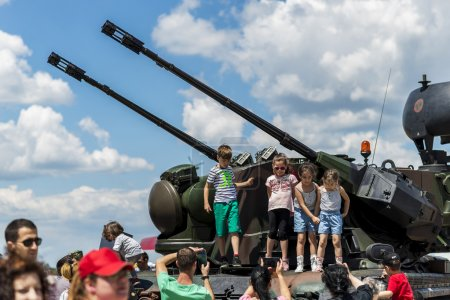 Children taking photos with anti-aircraft vehicle