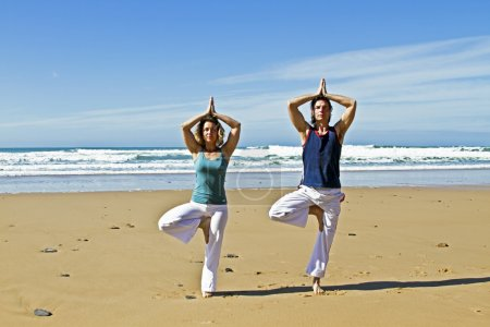Couple doing yoga excersises at the beach