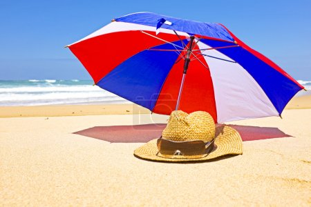 Photo for Straw hat, sunglasses and parasol at the beach - Royalty Free Image