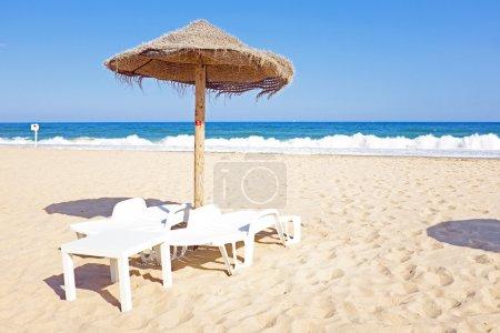 Sombrilla de paja y sillas de playa en la playa cerca de Lagos Portu