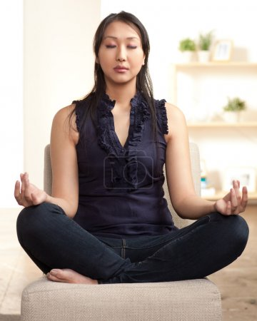 Photo for Young Asian woman sitting crossed legged in a meditation posture. - Royalty Free Image