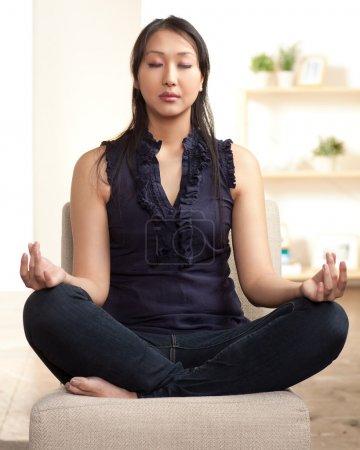 Photo pour Jeune femme asiatique assise traversé pattes dans une posture de méditation. - image libre de droit