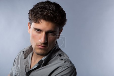 Sexy confident guy in studio on grey background