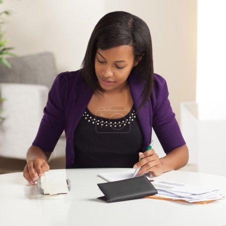 Cute young black female doing finances
