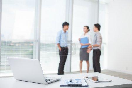Photo pour Gros plan du lieu de travail dans un bureau moderne avec l'entreprise derrière - image libre de droit