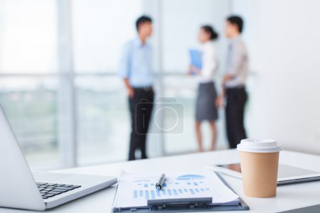 Photo for Close-up of office desk with business team behind - Royalty Free Image