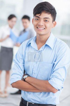 Photo pour Joyeux jeune leader regardant la caméra avec ses collègues derrière - image libre de droit