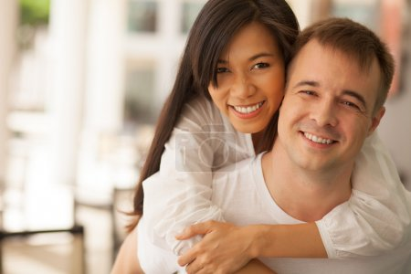 Photo for Portrait of young couple looking at camera and smiling at home - Royalty Free Image