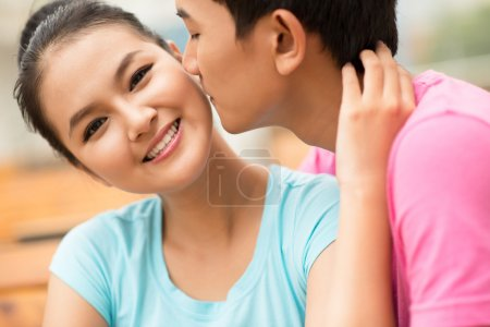 Photo for Close-up shot of a guy being about to kiss his girlfriend on the cheek - Royalty Free Image