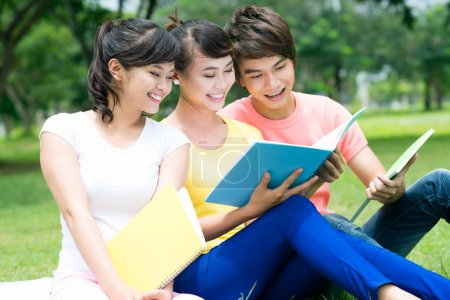 Photo for Smiling students having fun outdoors reading funny stuff - Royalty Free Image