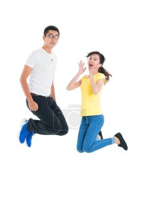 Foto de Retrato vertical de entusiasmados jóvenes saltando sobre fondo blanco - Imagen libre de derechos