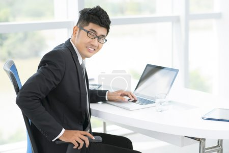 Photo for Portrait of a positive office manager at his workplace - Royalty Free Image