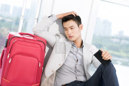 Photo for Portrait of young businessman with luggage touching his head in trouble - Royalty Free Image