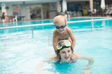 Photo for Boy sitting astride on his mothers shoulders while she swimming in the pool - Royalty Free Image