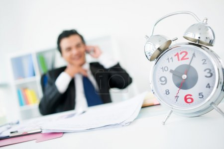 Photo for Happy businessman talking by the phone in his office while time ticking away on the clock - Royalty Free Image