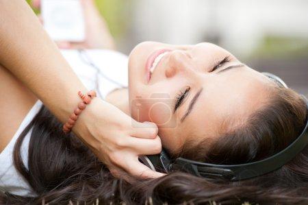 Photo pour Jeune fille couché avec casque - image libre de droit