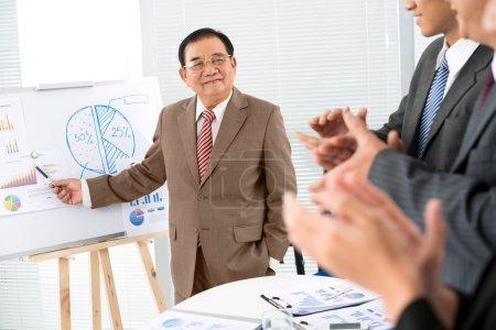 Photo pour Homme d'affaires montrant des graphiques et les autres applaudissements - image libre de droit