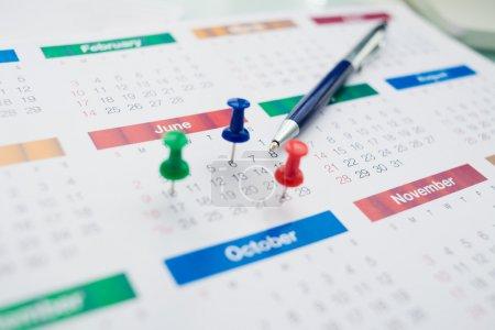 Photo pour Clôture-shot d'un calendrier d'entreprise avec des dates importantes soient marqués avec des épingles colorées - image libre de droit