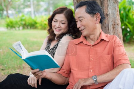 Photo for Senior enjoying summer weekend in park reading a book - Royalty Free Image