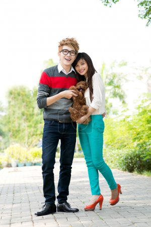 Photo for Portrait of a young couple with a dog in hands - Royalty Free Image