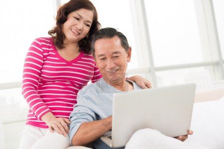 Photo pour Senior montrant quelque chose dans l'ordinateur à sa femme - image libre de droit