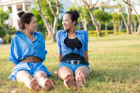 Photo for Portrait of girlfriends relaxing on the ground in the park - Royalty Free Image