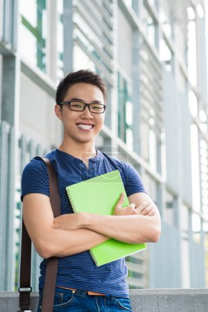 Photo for Vertical portrait of a cheerful male student standing outside - Royalty Free Image