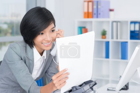 Photo for Copy-spaced image of a secretary calling by phone after faxing - Royalty Free Image