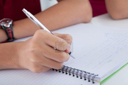 Photo pour Gros plan d'une main masculine tenant un stylo à bille et écrivant dans le bloc-notes - image libre de droit