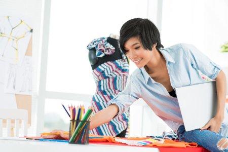 Photo pour Image d'une jeune modiste en choisissant un spectre de couleurs pour faire des croquis dans l'atelier - image libre de droit