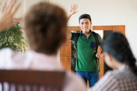 Photo pour Image d'un élève de quitter la pièce et dire au revoir à ses amis - image libre de droit
