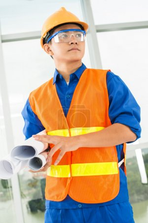 Photo for Vertical image of a concentrated architect holding blueprints - Royalty Free Image