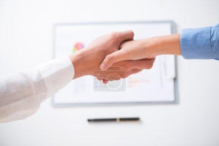 Photo pour Poignée de main humaine après avoir signé un contrat vu ci-dessous - image libre de droit