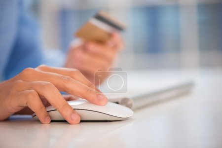 Close-shot of a human hand clicking a computer mouse on the workplace