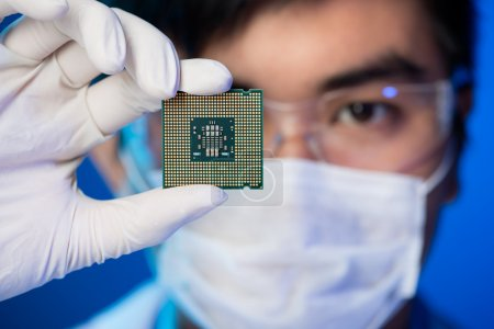 Photo for Cropped image of an engineer showing a computer microchip on the foreground - Royalty Free Image