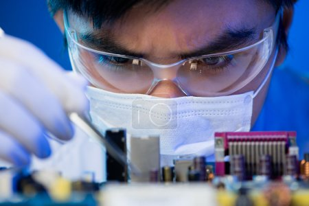 Photo for Close-up image of an engineer concentrated on electronic assembling on the foreground - Royalty Free Image