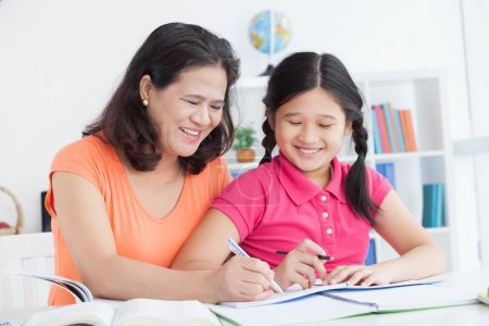 A mother teaching her daughter to write in the cor...