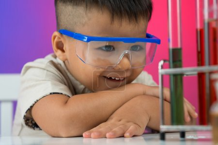 Photo for Close-up image of a little boy looking at the chemical substance with interest in the lab - Royalty Free Image