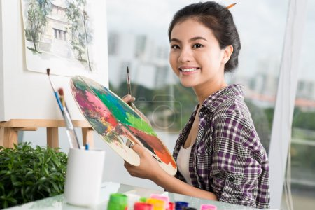 Photo for Portrait of a happy artist with a palette in hands on the foreground - Royalty Free Image