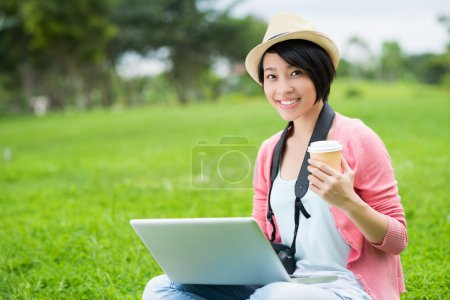 Photo for Copy-spaced portrait of a cheerful young photographer with a laptop and a coffecup smiling and posing at camera outside - Royalty Free Image