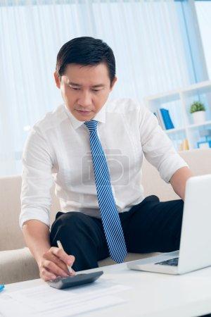 Photo pour Verticale de l'image d'un jeune conseiller financier au travail sur le premier plan - image libre de droit