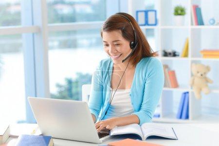 Photo pour Image d'une jeune fille à l'aide de la technologie de skype à la maison sur le premier plan - image libre de droit