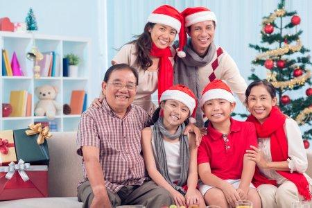 Photo pour Portrait des membres de la famille heureuse en caps santa regardant la caméra avec des sourires - image libre de droit