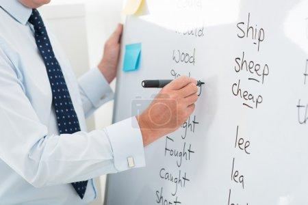 Photo pour Gros plan d'un enseignant de sexe masculin écrit des mots anglais sur le tableau blanc - image libre de droit