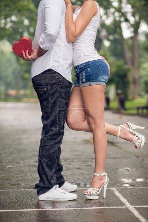 Photo pour Cropped image d'un jeune couple en amour où un copain tenant une boîte cadeau pour sa petite amie à l'extérieur - image libre de droit